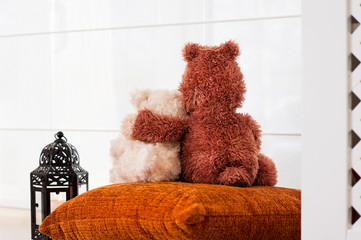 Two embracing loving teddy bears sitting on window-sill. Love .