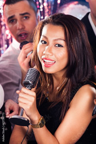 Woman Singing Into Microphone At Karaoke Party
