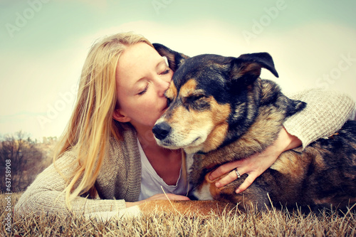 Leinwanddruck Bild Woman Tenderly Hugging and Kissing Pet Dog