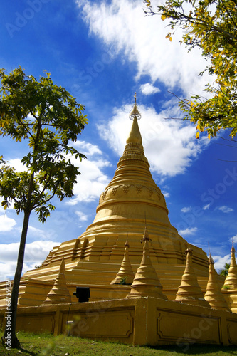 Yellow pagoda and tree blue sky in Thailand