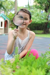 girl with magnifying glass in garden