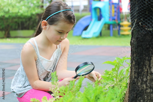 girl with magnifying glass in garden explore
