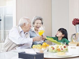 little asian girl toasting with grandparents