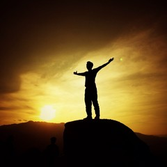 man silhouette with her hand raised in the sunset