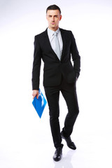 Studio shot of a businessman with blue folder on gray background