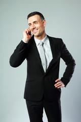 Cheerful businessman talking on the phone over gray background
