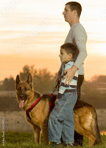 Dad and son and German shepherd in nature watching the sunset
