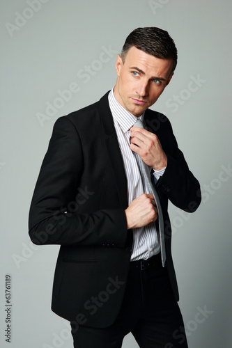 Handsome businessman straightening his tie on gray background