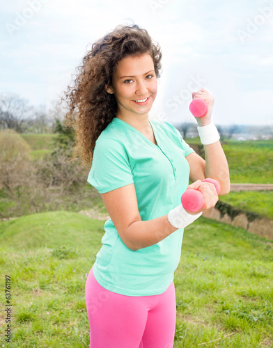 Portrait of Beautiful young woman exercising with weights in the