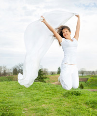 Young happy woman jumps and holding a white piece of cloth in th