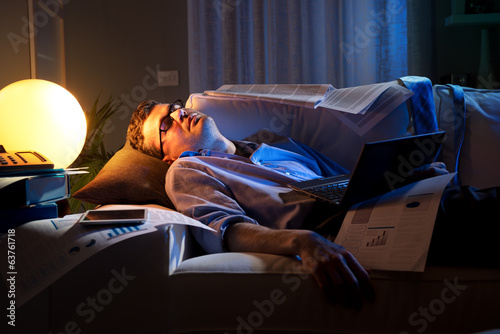 Overworked businessman on sofa