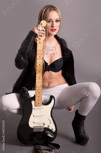 girl with tattoos posing with a guitar