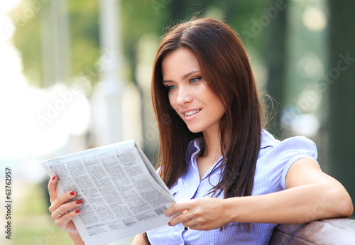 A pretty business woman reading newspaper outside