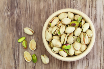 Pistachio nuts in wooden bowl with copy space