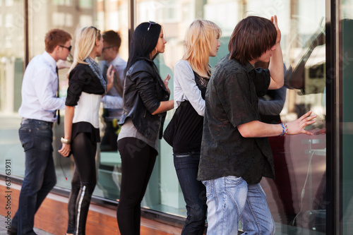 Young people looking through the mall window