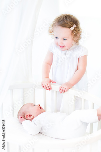 Beautiful toddler girl with curly hair with his brother