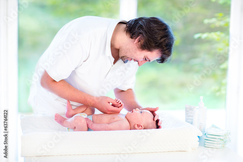 Young happy father playing with his newborn baby son