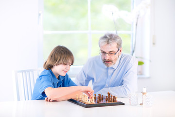 Cute happy boy playing chess with his grandfather