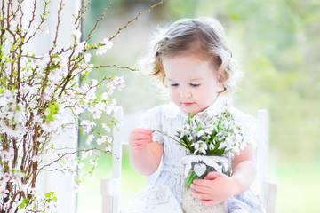 Beautiful toddler girl in white dress sitting in white room