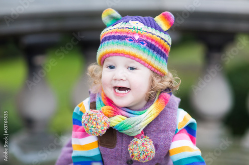 Portrait of a happy toddler girl in striped colorful knitted hat