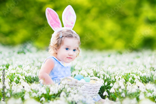 Funny toddler girl wearing bunny ears playing with Easter eggs