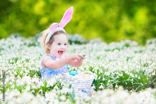 Pretty toddler girl in rabbit ears in first spring flowers