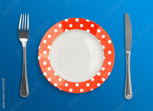 polka dot red plate with fork and knife top view on blue backgro