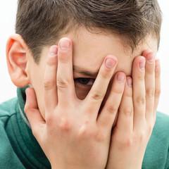 подросток подглядывает сквозь пальцы, закрывающие лицо