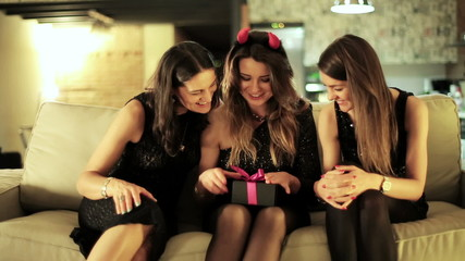 young woman opening gift at the bachelorette party