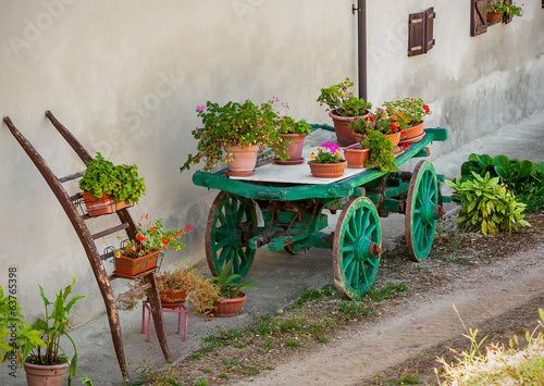 Pots with flowers on wooden cart in Italy.