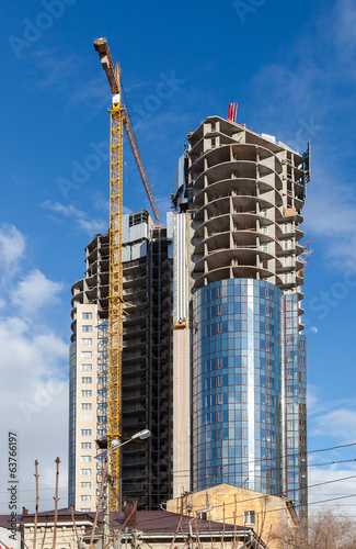 Tall buildings under construction with cranes against a blue sky