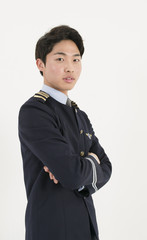 Asian airline pilot with his arms crossed