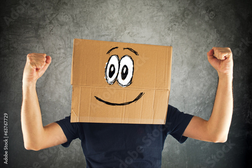 Happy smiling man with cardboard box on his head and raised fist