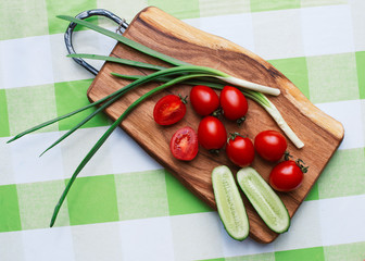 red tomatoes and green onions on cutting board closeup