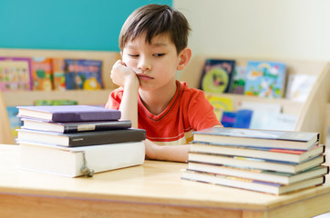 Little boy reading book on table at home with boring face