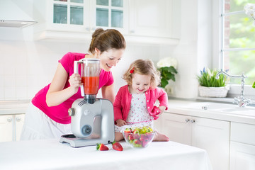 Beautiful mother with toddler girl making fresh srraberry juice