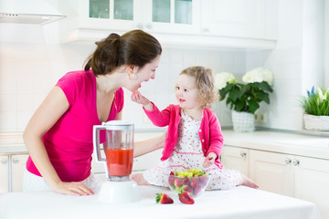Mother and her toddler girl making fresh srraberry juice