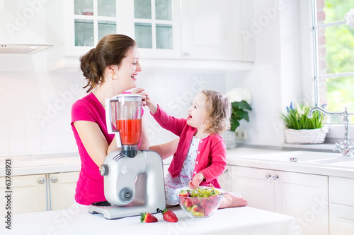 Beautiful mother with her happy toddler girl preparing breakfast
