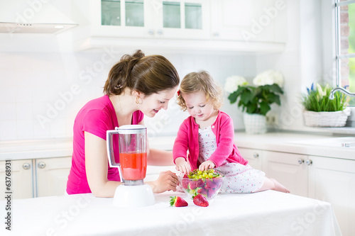 Mother with happy toddler girl preparing fresh srraberry juice