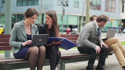 Businesspeople working on laptop and sitting on street bench