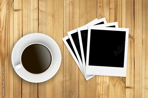 Cup of coffee and old photo paper on wooden background