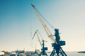 Harbor cranes against blue sky colorized image