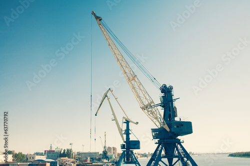Harbor cranes against blue sky colorized image