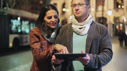 Couple checking map on tablet and walking on street at night, st