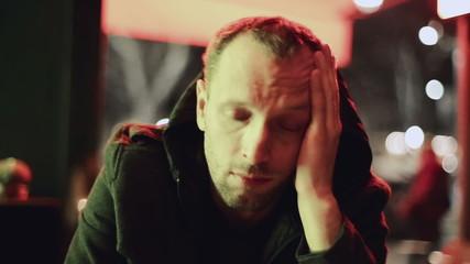 Sad man sitting alone in pub at night, steadycam shot