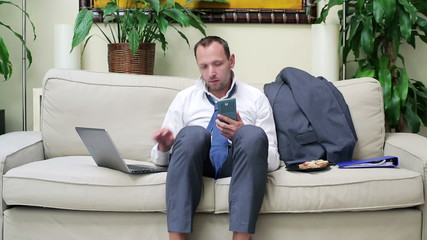 businessman sitting on the sofa and comparing data on his laptop