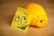 Post-it note with smiley face sticked on lemon