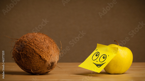 Apple with post-it note looking at coconut
