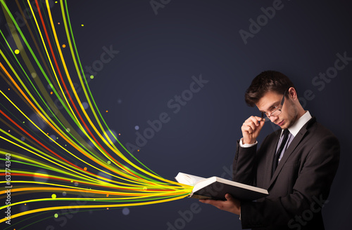 Handsome man reading a book while colorful lines are coming out