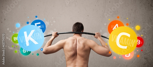 skinny guy lifting colorful vitamin weights
